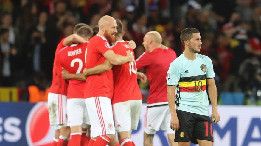 Belgium's Eden Hazardstands on the pitch as Wales players celebrate at the end of the Euro 2016 quarterfinal soccer match between Wales and Belgium, at the Pierre Mauroy stadium in Villeneuve d'Ascq, near Lille, France, Friday, July 1, 2016. Wales won 3-1. (AP Photo/Petr David Josek)