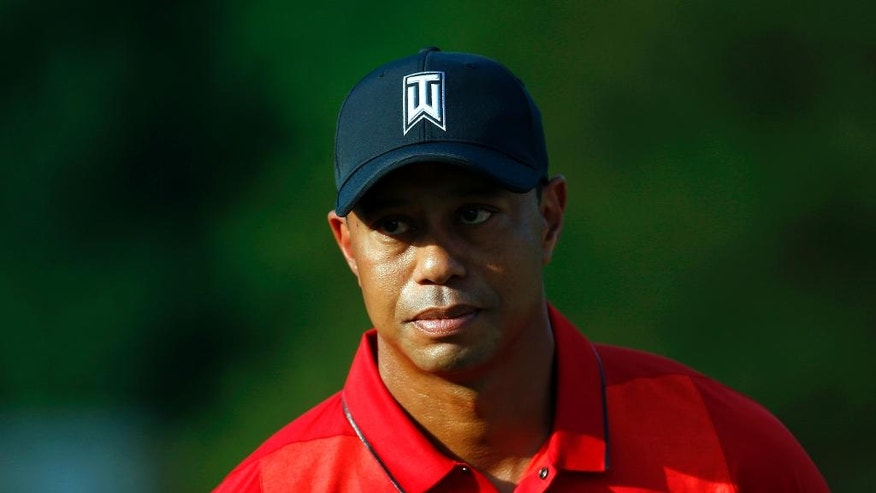 FILE - In this June 26, 2016, file photo, Tiger Woods stands on the 18th green during a trophy ceremony for Quicken Loans National PGA golf tournament winner Billy Hurley III in Bethesda, Md. Organizers say Friday, July 1, 2016, that Woods has withdrawn from the British Open at Royal Troon. (AP Photo/Patrick Semansky, File)