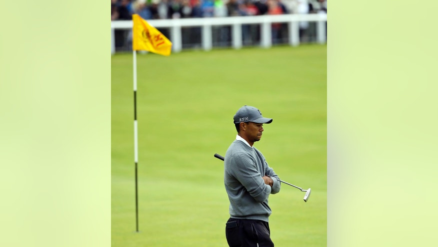FILE - In this July 16, 2015, file photo, United States' Tiger Woods walks on the 18th green during the first round of the British Open Golf Championship at the Old Course, St. Andrews, Scotland. Organizers say Friday, July 1, 2016, that Woods has withdrawn from the British Open at Royal Troon. (AP Photo/David J. Phillip, File)