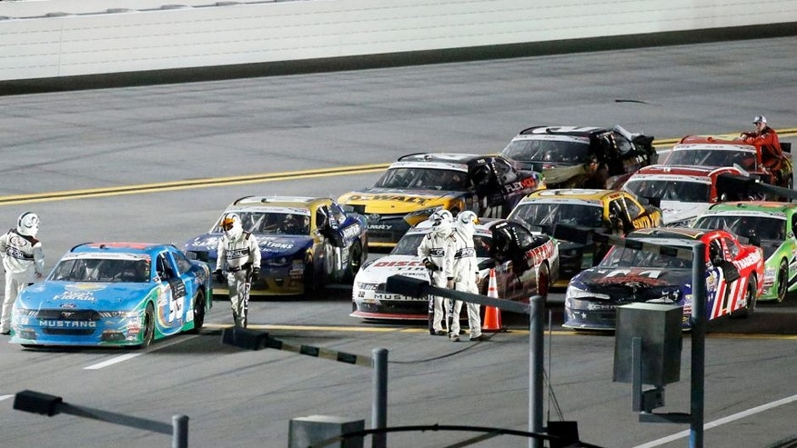 The field of cars are frozen near pit road before the finish line while officials determine the winner of the NASCAR Xfinity Series auto race at Daytona International Speedway, Friday, July 1, 2016, in Daytona Beach, Fla. Aric Almirola, front left, was declared the winner of race when NASCAR determined he was the leader when the caution flag froze the field shortly before the finish line. (AP Photo/Wilfredo Lee)