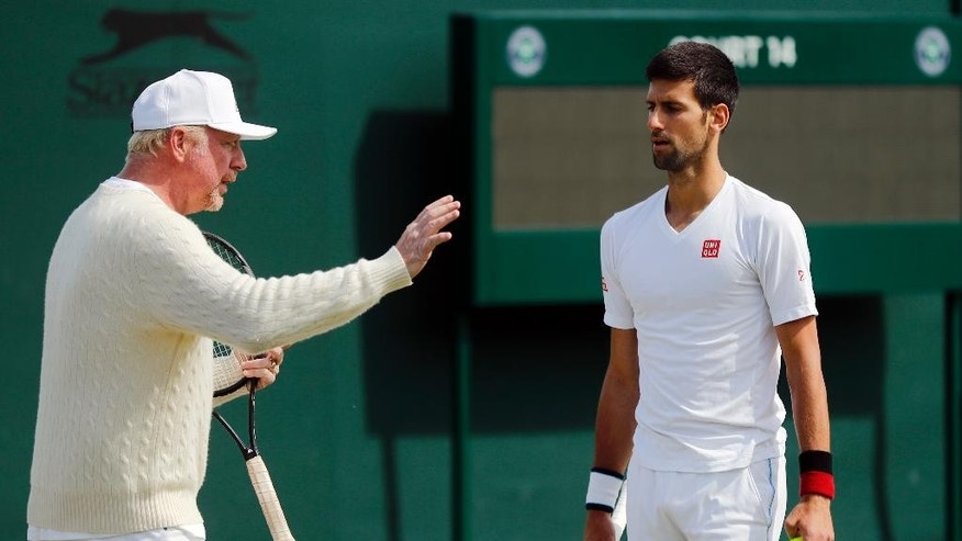 Novak Djokovic of Serbia, right, speaks with his coach Boris Becker before resuming his men's singles match against Sam Querrey of the U.S on day six of the Wimbledon Tennis Championships in London, Saturday, July 2, 2016. (AP Photo/Ben Curtis)
