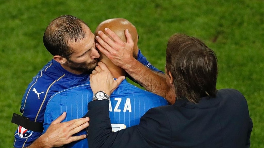 Italy's Giorgio Chiellini, left, kisses his teammate Simone Zaza as he leaves the pitch while coach Antonio Conte looks during the Euro 2016 quarterfinal soccer match between Germany and Italy, at the Nouveau Stade in Bordeaux, France, Saturday, July 2, 2016. (AP Photo/Michael Sohn)
