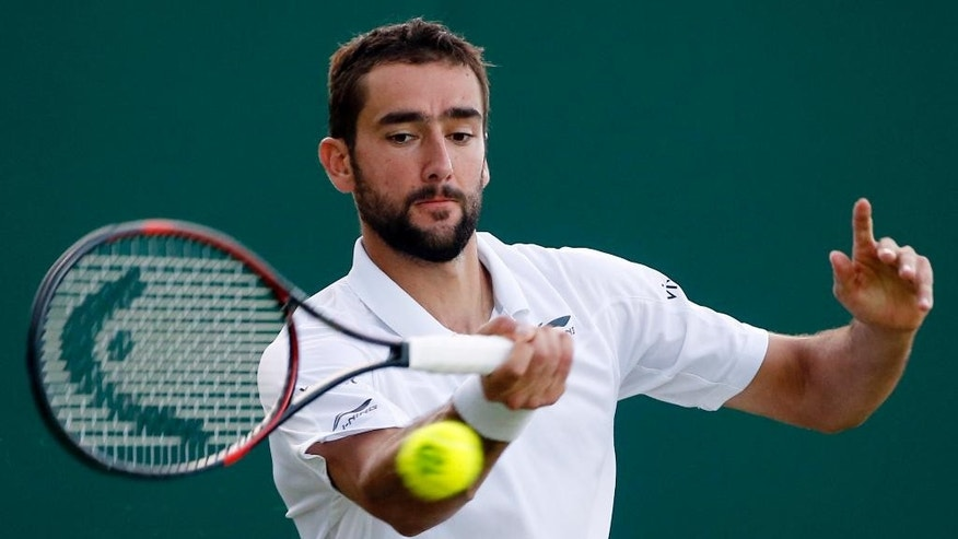Marin Cilic of Croatia returns to Lukas Lacko of Slovakia during their men's singles match on day five of the Wimbledon Tennis Championships in London, Friday, July 1, 2016. (AP Photo/Alastair Grant)