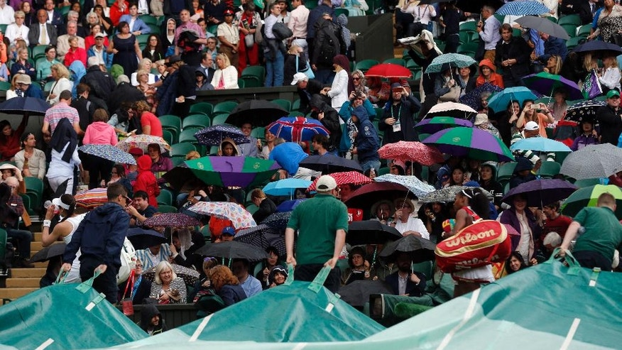 Serena Williams of the U.S leaves the court as the rain starts during her women's singles match against Christina McHale of the US on day five of the Wimbledon Tennis Championships in London, Friday, July 1, 2016. (AP Photo/Ben Curtis)