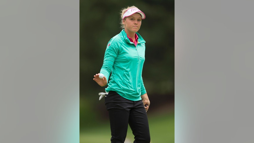 Brooke Henderson, of Canada, acknowledges fans after putting for par on the first hole during the final round of the LPGA Cambia Portland Classic golf tournament Sunday, July 3, 2016, in Portland, Ore. (AP Photo/Troy Wayrynen)