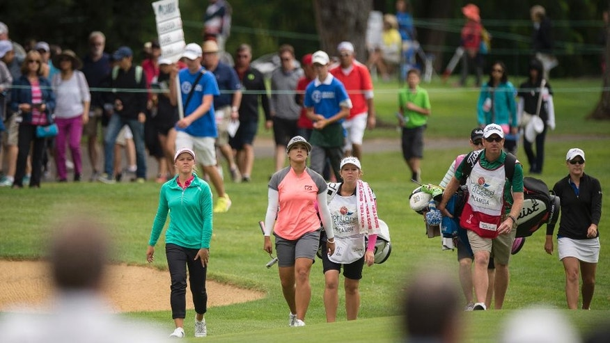 Brooke Henderson, left, of Canada, Mariajo Uribe, center, of Colombia, and Austin Ernst, far right, of the United States, approach the putting green on the second hole during the final round of the LPGA Cambia Portland Classic golf tournament Sunday, July 3, 2016, in Portland, Ore. (AP Photo/Troy Wayrynen)
