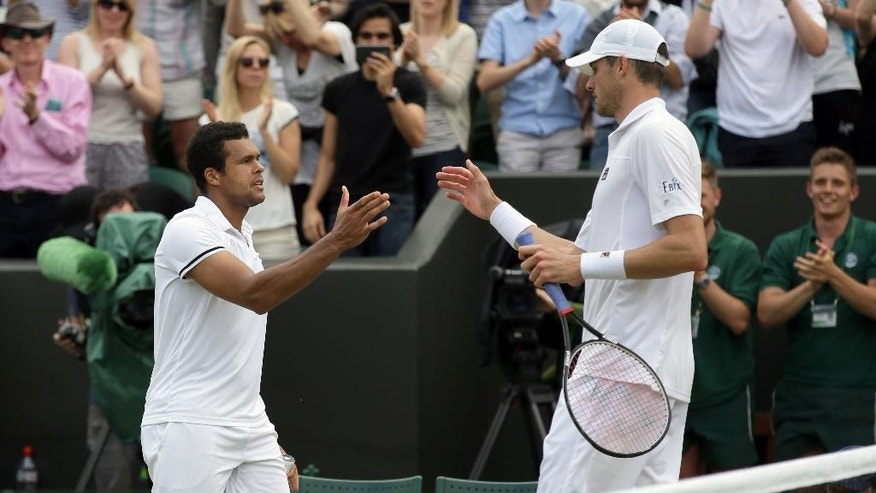 Jo-Wilfried Tsonga of France, left, shakes hands with John Isner of the U.S after beating him in their men's singles match on day seven of the Wimbledon Tennis Championships in London, Sunday, July 3, 2016. (AP Photo/Tim Ireland)