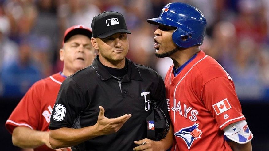 Toronto Blue Jays designated hitter Edwin Encarnacion exchanges words with umpire Vic Carapazza, left, after Encarnacion was ejected from the game over a call-out dispute on strikes during the first inning of a baseball against the Cleveland Indians in Toronto., Friday, July 1, 2016. (Frank Gunn/The Canadian Press via AP)
