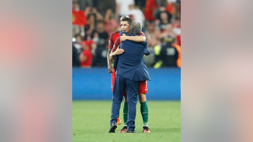 Portugal coach Fernando Santos, back to camera, hugs Cristiano Ronaldo at the end of the Euro 2016 quarterfinal soccer match between Poland and Portugal, at the Velodrome stadium in Marseille, France, Thursday, June 30, 2016. Portugal won 5-3 in a penalty shootout. (AP Photo/Frank Augstein)