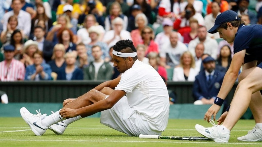 Nick Kyrgios of Australia adjusts his socks during his men's singles match against Andy Murray of Britain on day eight of the Wimbledon Tennis Championships in London, Monday, July 4, 2016. (AP Photo/Kirsty Wigglesworth)