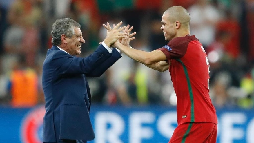 Portugal coach Fernando Santos, left, congratulates Pepe, at the end of the Euro 2016 quarterfinal soccer match between Poland and Portugal, at the Velodrome stadium in Marseille, France, Thursday, June 30, 2016. Portugal won 5-3 in a penalty shootout. (AP Photo/Frank Augstein)