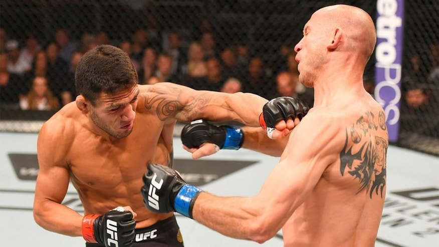 ORLANDO, FL - DECEMBER 19: (L-R) Rafael dos Anjos punches Donald Cerrone in their UFC lightweight title bout during the UFC Fight Night event at the Amway Center on December 19, 2015 in Orlando, Florida. (Photo by Josh Hedges/Zuffa LLC/Zuffa LLC via Getty Images)