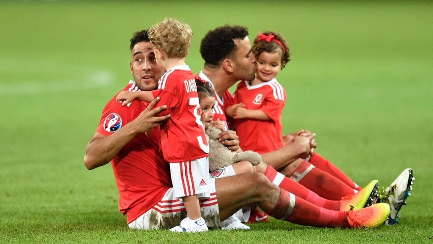 Wales' James Chester, left, and Wales' Hal Robson Kanu play with their children on the pitch at the end of the Euro 2016 quarterfinal soccer match between Wales and Belgium, at the Pierre Mauroy stadium in Villeneuve d'Ascq, near Lille, France, Friday, July 1, 2016. Wales won 3-1. (AP Photo/Martin Meissner)