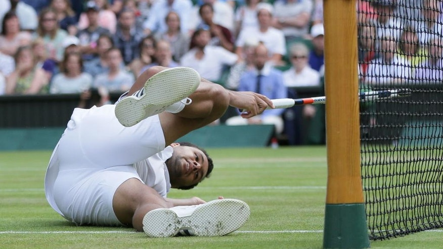 Jo-Wilfried Tsonga of France falls over next to the net as he plays against Andy Murray of Britain during their men's singles quarterfinal match on day ten of the Wimbledon Tennis Championships in London,  Wednesday, July 6, 2016. (AP Photo/Tim Ireland)