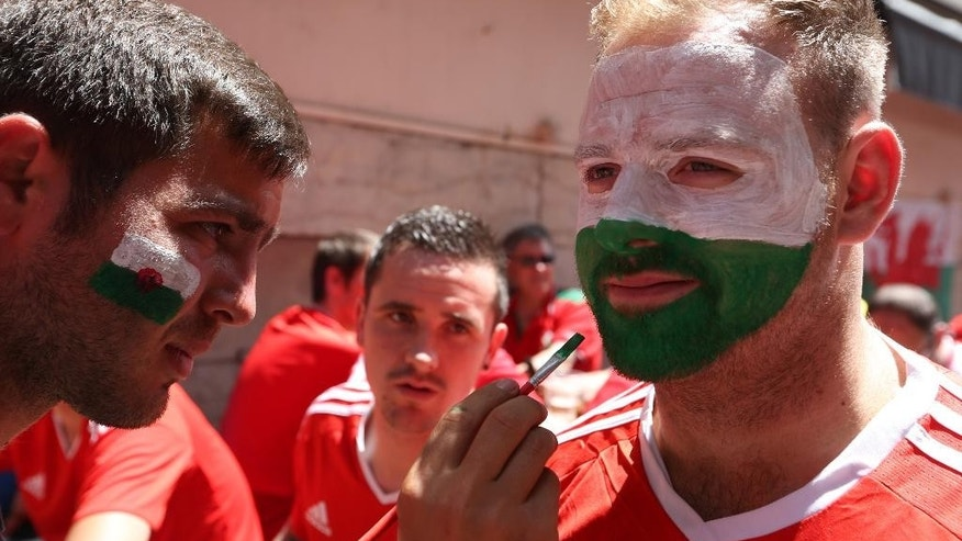 A man paints the flag of Wales on the face of a fan in central Lyon, France, Wednesday, July 6, 2016, prior the Euro 2016 semifinal soccer match between Portugal and Wales. (AP Photo/Thanassis Stavrakis)