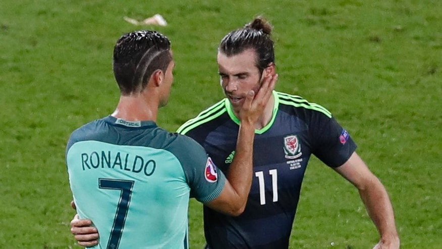 Portugal's Cristiano Ronaldo, left, comforts Wales' Gareth Bale after Portugal won 2-0  during the Euro 2016 semifinal soccer match between Portugal and Wales, at the Grand Stade in Decines-­Charpieu, near Lyon, France, Wednesday, July 6, 2016. (AP Photo/Michael Sohn)