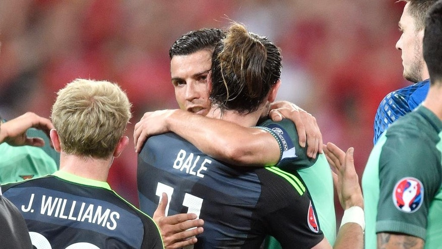 Wales' Gareth Bale, center right, and Portugal's Cristiano Ronaldo embrace each other at the end of the Euro 2016 semifinal soccer match between Portugal and Wales, at the Grand Stade in Decines-­Charpieu, near Lyon, France, Wednesday, July 6, 2016. Portugal won 2-0. (AP Photo/Martin Meissner)