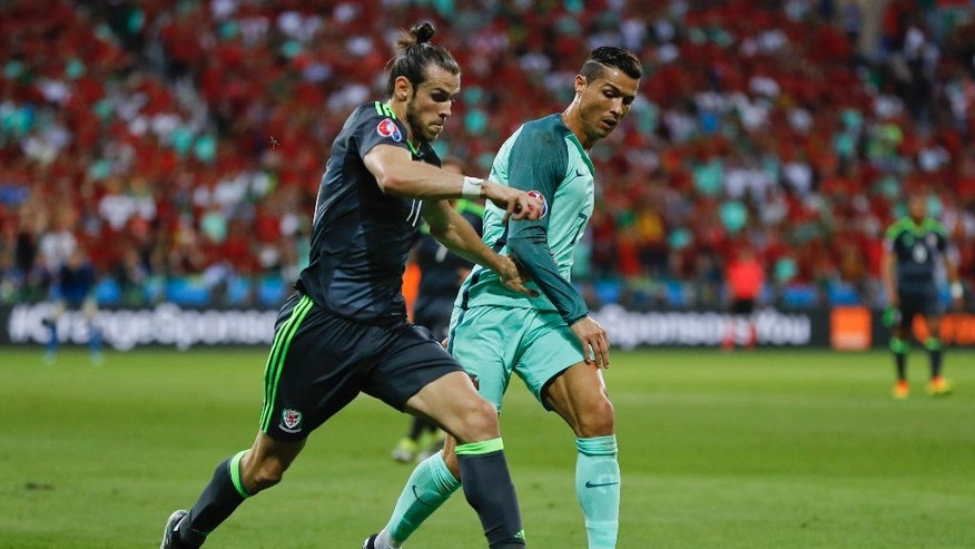 Wales' Gareth Bale, left, and Portugal's Cristiano Ronaldo compete for the ball during the Euro 2016 semifinal soccer match between Portugal and Wales, at the Grand Stade in Decines-Charpieu, near Lyon, France, Wednesday, July 6, 2016. (AP Photo/Frank Augstein)
