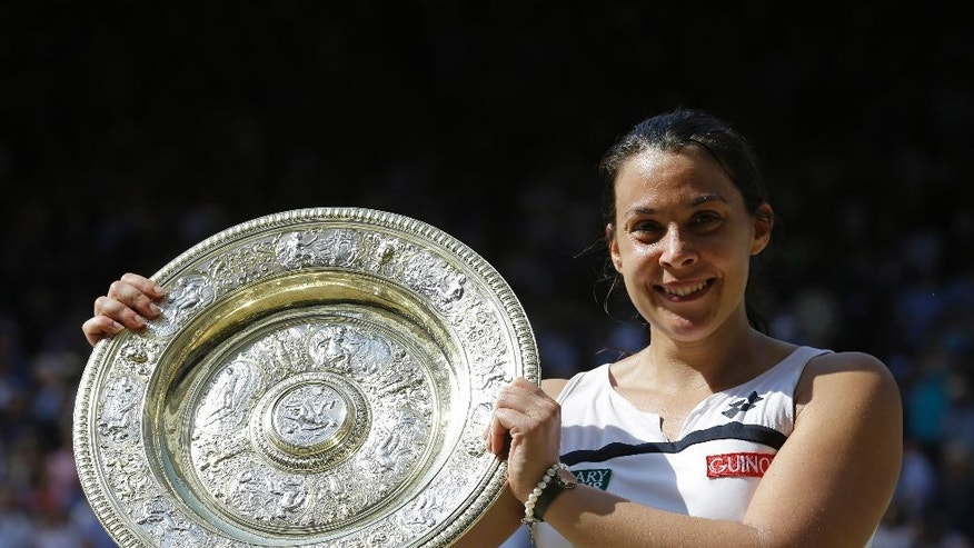 """FILE - A  Saturday, July 6, 2013 file photo showing Marion Bartoli of France smiling as she holds the trophy after winning the Women's singles final match against Sabine Lisicki of Germany at the All England Lawn Tennis Championships in Wimbledon, London. Three years after winning the title at Wimbledon, Marion Bartoli said she has contracted an unknown virus and her life is an """"absolute nightmare."""" The 31-year-old Frenchwoman is now extremely thin and said it's because she is ill. (AP Photo/Anja Niedringhaus, File)"""