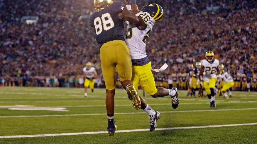 Michigan defensive back Jourdan Lewis, right, interferes with Notre Dame wide receiver Corey Robinson in as he attempts a catch in the end zone during the first half of an NCAA college football game in South Bend, Ind. in 2014.