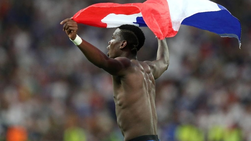 France's Paul Pogba celebrates holding the French flag after the Euro 2016 semifinal soccer match between Germany and France, at the Velodrome stadium in Marseille, France, Thursday, July 7, 2016. (AP Photo/Thanassis Stavrakis)