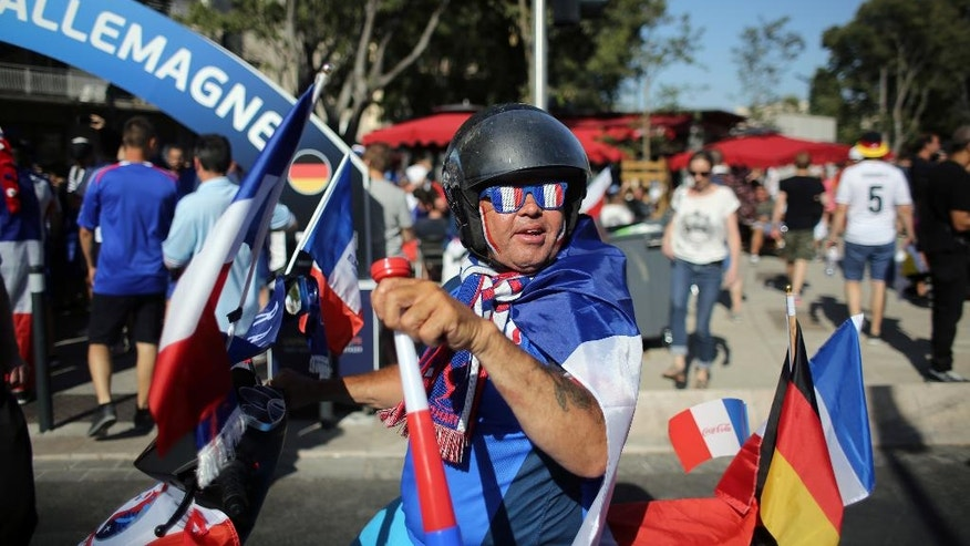 A France supporter rides a scooter near the Velodrome stadium in Marseille, prior to the Euro 2016 semifinal soccer match between France and Germany, Thursday, July 7, 2016. (AP Photo/Thibault Camus)