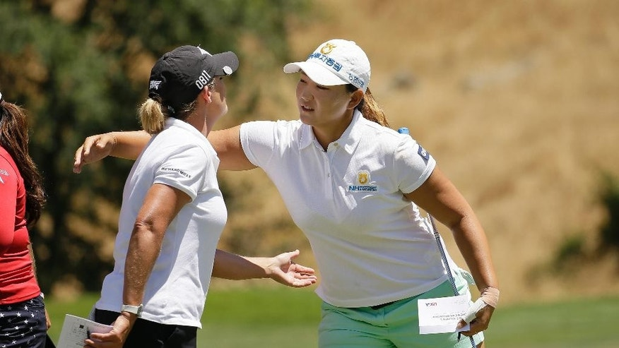 Mirim Lee, right, of South Korea, is greeted by Cristie Kerr, left, on the ninth green after finishing the first round of the U.S. Women's Open golf tournament at CordeValle on Thursday, July 7, 2016, in San Martin, Calif. Lee shot an 8-under-par 64. (AP Photo/Eric Risberg)