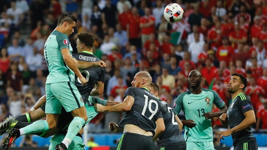 Portugal's Cristiano Ronaldo scores on a header during the Euro 2016 semifinal soccer match between Portugal and Wales, at the Grand Stade in Decines-Charpieu, near Lyon, France, Wednesday, July 6, 2016. (AP Photo/Frank Augstein)