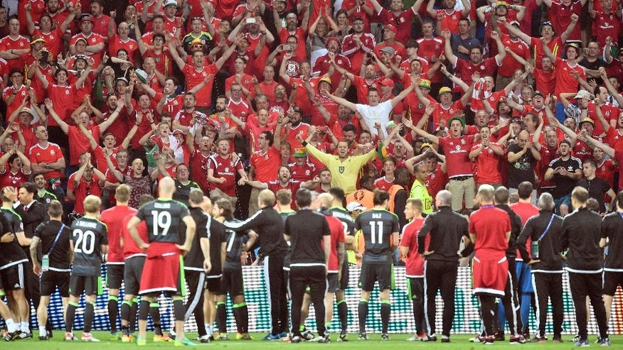 Wales players stand in front of their supporters at the end of the Euro 2016 semifinal soccer match between Portugal and Wales, at the Grand Stade in Decines-­Charpieu, near Lyon, France, Wednesday, July 6, 2016. Portugal won 2-0. (AP Photo/Martin Meissner)
