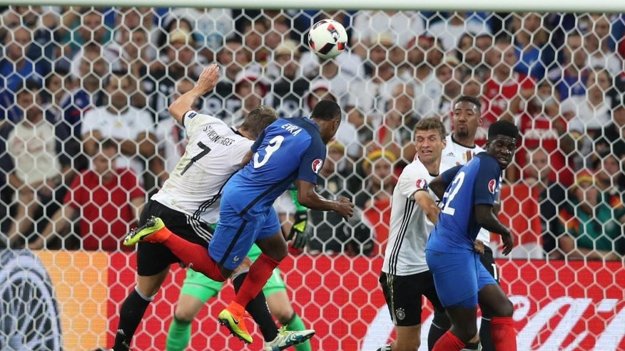 Germany's Bastian Schweinsteiger, left, jumps for a header with France's Patrice Evra during the Euro 2016 semifinal soccer match between Germany and France, at the Velodrome stadium in Marseille, France, Thursday, July 7, 2016. (AP Photo/Thanassis Stavrakis)