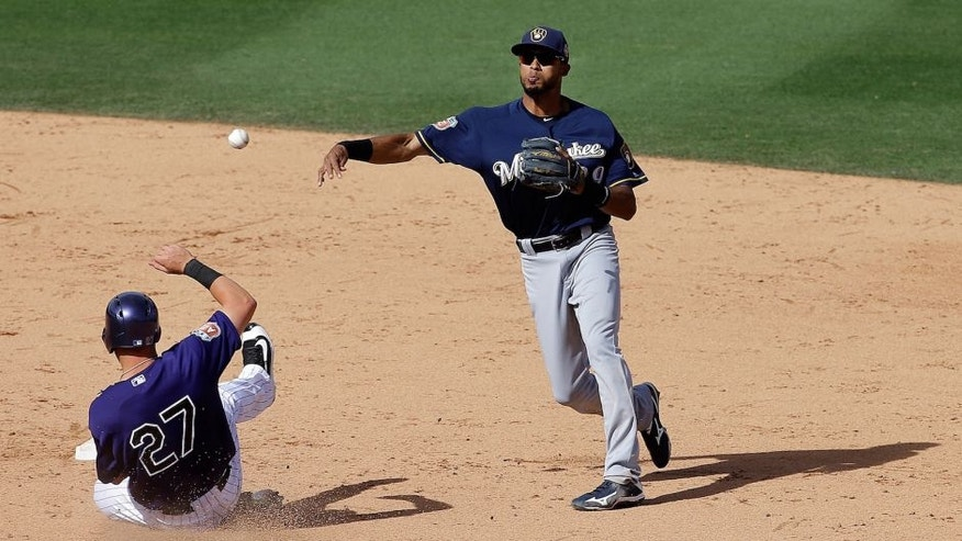 <p>Milwaukee Brewers shortstop Yadiel Rivera, right, throws to first base after forcing out Colorado Rockies' Trevor Story on a double play ball hit by Carlos Gonzalez during the sixth inning of a spring training baseball game.</p>