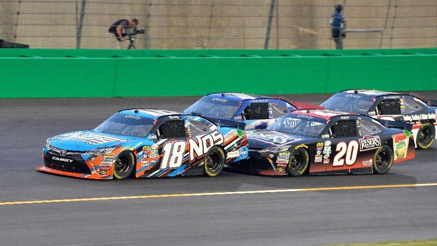 Kyle Busch (18) is drafted by Erik Jones (20) going into the first turn during the NASCAR Xfinity Series auto race at Kentucky Speedway, Friday, July 8, 2016, in Sparta, Ky. (AP Photo/Timothy D. Easley)