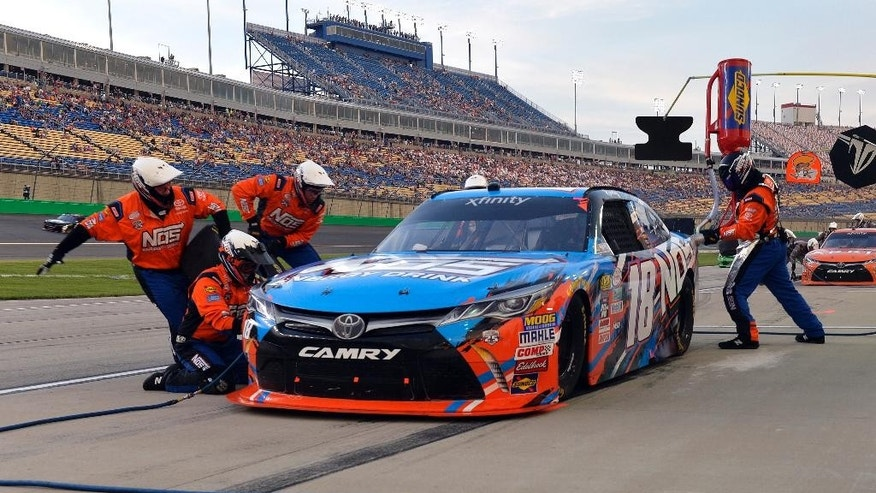 The pit crew of Kyle Busch changes his right side tires and tops off the fuel during a caution in the NASCAR Xfinity Series auto race at Kentucky Speedway, Friday, July 8, 2016, in Sparta Ky. (AP Photo/Timothy D. Easley)