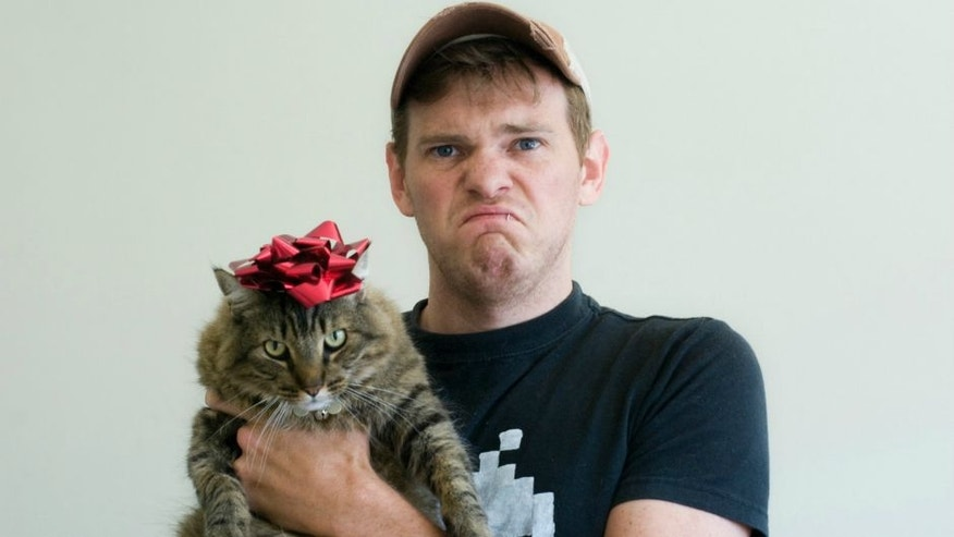 An unhappy man wearing t-shirt and baseball cap holds large cat with red bow on it's head.