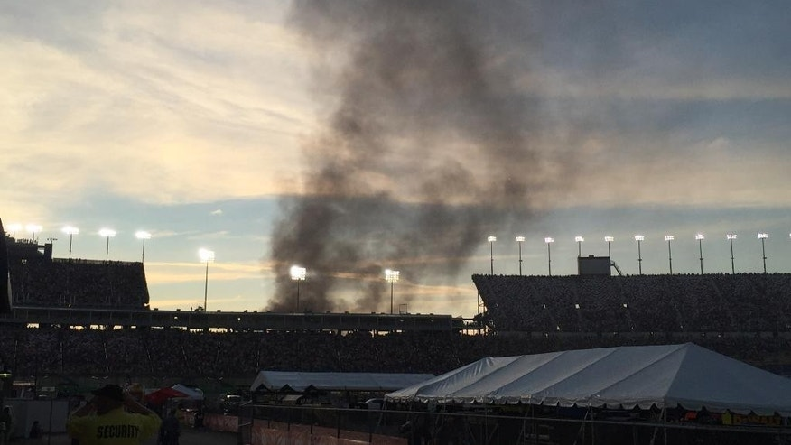 Smoke rises over the main grandstand from a vehicle fire in the platinum parking lot at the NASCAR Sprint Cup Series auto race at Kentucky Speedway, Saturday, July 9, 2016 in Sparta, Ky. (AP Photo/Gary Graves)