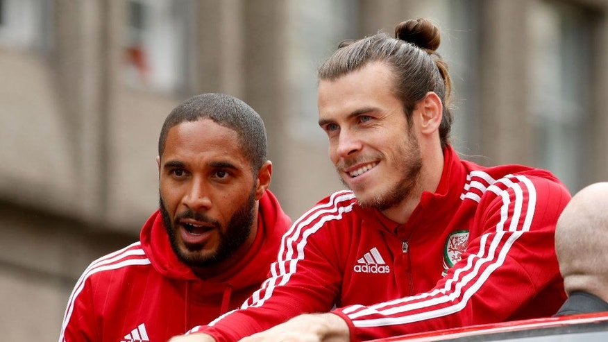 Wales soccer players ride an open top bus, with front left to right, Ashley Williams, Gareth Bale, as they acknowledge the crowd of fans during their homecoming in Cardiff City centre, Wales, Friday July 8, 2016.  Wales return home to a hero's welcome after unexpectedly reaching the semi-finals of the Euro 2016 soccer championships knocked out by Portugal but refreshing Welsh pride. (Paul Harding / PA via AP)