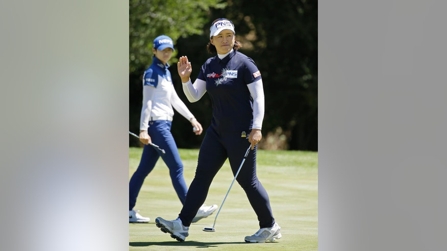 Amy Yang, of South Korea, waves after making a birdie putt on the sixth green during the third round of the U.S. Women's Open golf tournament at CordeValle Saturday, July 9, 2016, in San Martin, Calif. In the background is Sung Hyun Park, of South Korea. (AP Photo/Eric Risberg)