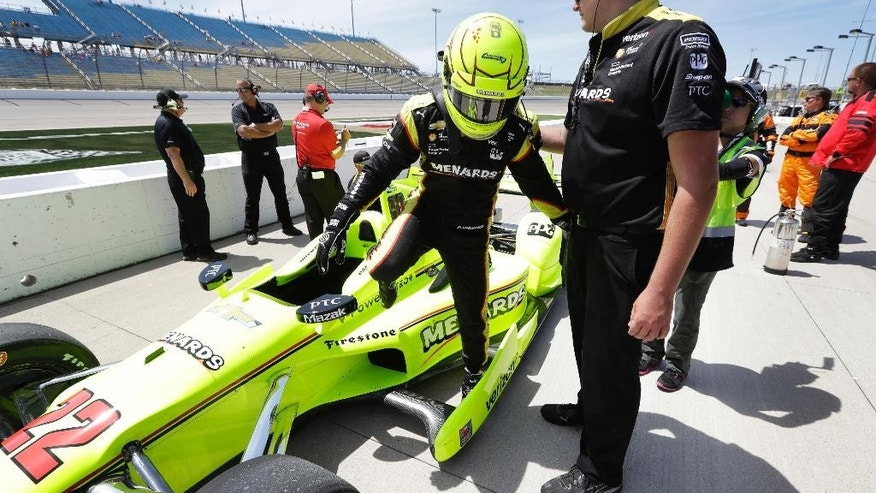Simon Pagenaud climbs out of his car after winning the pole position for the IndyCar Series auto race Saturday, July 9, 2016, at Iowa Speedway in Newton, Iowa. (AP Photo/Charlie Neibergall)