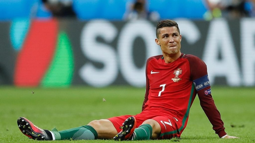 Portugal's Cristiano Ronaldo sits on the pitch after a challenge during the Euro 2016 final soccer match between Portugal and France at the Stade de France in Saint-Denis, north of Paris, Sunday, July 10, 2016. (AP Photo/Frank Augstein)