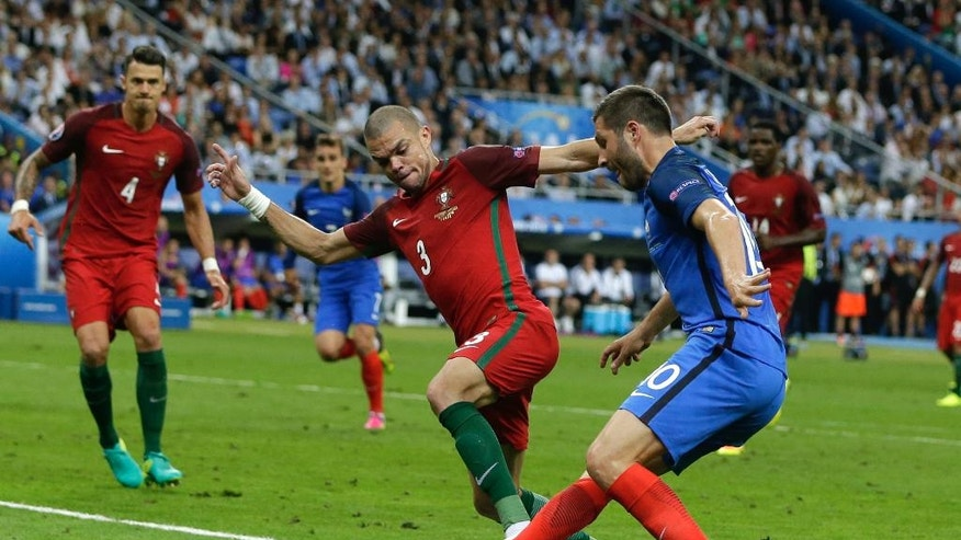 France's Andre Pierre Gignac, right, is challenged by Portugal's Pepe during the Euro 2016 final soccer match between Portugal and France at the Stade de France in Saint-Denis, north of Paris, Sunday, July 10, 2016. (AP Photo/Thanassis Stavrakis)