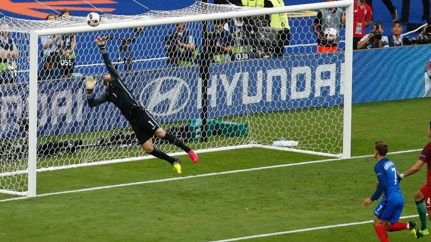 Portugal goalkeeper Rui Patricio jumps for a ball headed by France's Antoine Griezmann, right,  during the Euro 2016 final soccer match between Portugal and France at the Stade de France in Saint-Denis, north of Paris, Sunday, July 10, 2016. (AP Photo/Michael Sohn)