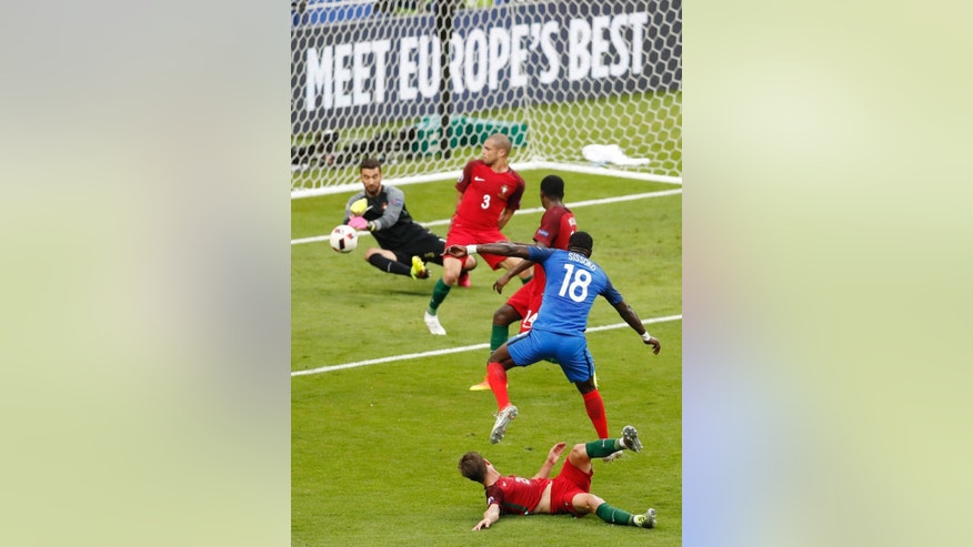 Portugal goalkeeper Rui Patricio, left, deflects a shot by France's Moussa Sissoko during the Euro 2016 final soccer match between Portugal and France at the Stade de France in Saint-Denis, north of Paris, Sunday, July 10, 2016. (AP Photo/Michael Sohn)