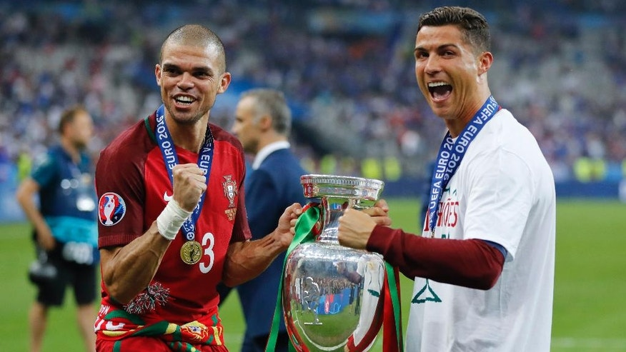 Portugal's Cristiano Ronaldo, right, and Pepe celebrate with the trophy at the end of the Euro 2016 final soccer match between Portugal and France at the Stade de France in Saint-Denis, north of Paris, Sunday, July 10, 2016. Portugal won 1-0. (AP Photo/Frank Augstein)