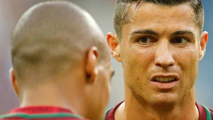 Portugal's Cristiano Ronaldo, right, looks at Joao Mario shortly before being taken off injured during the Euro 2016 final soccer match between Portugal and France at the Stade de France in Saint-Denis, north of Paris, Sunday, July 10, 2016. (AP Photo/Michael Probst)