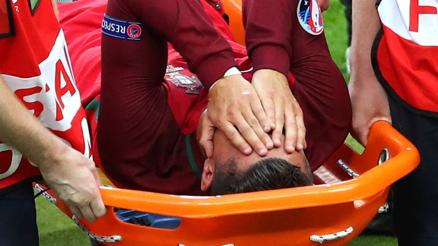 Portugal's Cristiano Ronaldo covers his face as he is stretchered off the pitch after suffering an injury during the Euro 2016 final soccer match between Portugal and France at the Stade de France in Saint-Denis, north of Paris, Sunday, July 10, 2016. (AP Photo/Thibault Camus)