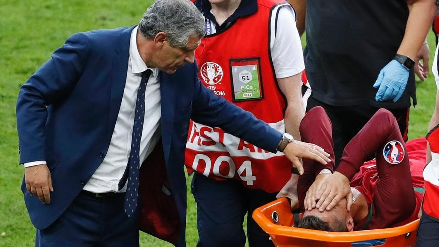 Portugal coach Fernando Santos, left, comforts Portugal's Cristiano Ronaldo who suffered an injury during the Euro 2016 final soccer match between Portugal and France at the Stade de France in Saint-Denis, north of Paris, Sunday, July 10, 2016. (AP Photo/Michael Sohn)