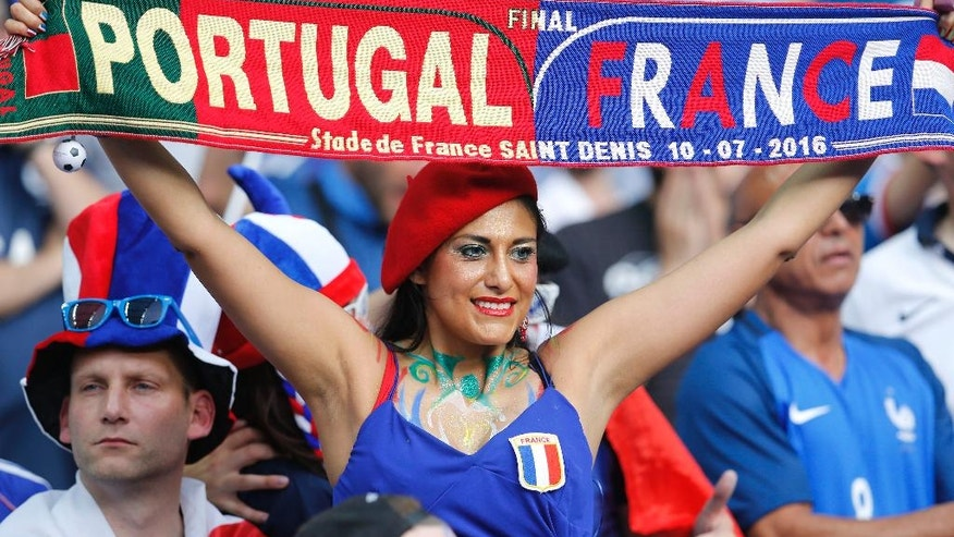 A French supporter holds up a scarf as she waits for the start of the Euro 2016 final soccer match between Portugal and France at the Stade de France in Saint-Denis, north of Paris, Sunday, July 10, 2016. (AP Photo/Michael Probst)