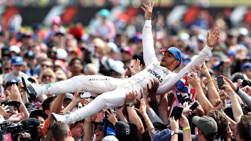 NORTHAMPTON, ENGLAND - JULY 10: Lewis Hamilton of Great Britain and Mercedes GP celebrates his win by crowdsurfing with the fans during the Formula One Grand Prix of Great Britain at Silverstone on July 10, 2016 in Northampton, England. (Photo by Mark Thompson/Getty Images)