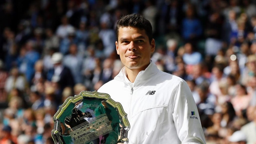 Milos Raonic of Canada holds his runner's up trophy after being beaten by Andy Murray of Britain in the men's singles final on day fourteen of the Wimbledon Tennis Championships in London, Sunday, July 10, 2016. (AP Photo/Kirsty Wigglesworth)
