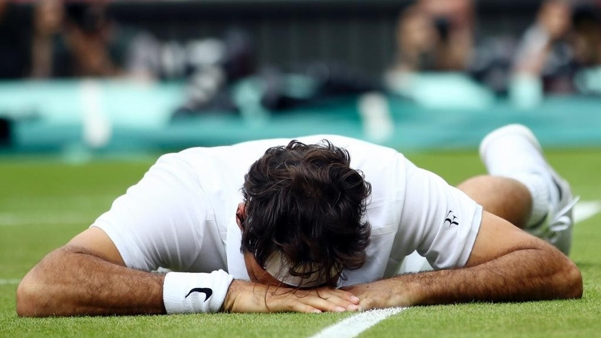 Roger Federer of Switzerland falls over during his men's semifinal singles match against Milos Raonic of Canada on day twelve of the Wimbledon Tennis Championships in London, Saturday, July 9, 2016. (Clive Brunskill/Pool Photo via AP)